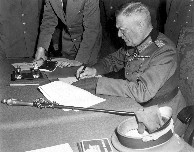 Feldmarszałek Wilhelm Keitel podpisuje warunki poddania niemieckiej armii w siedzibie rosyjskiej kwatery w Berlinie 7 maja 1945 roku (fot. Lt. Moore (US Army) - National Archives and Records Administration, źródło: domena publiczna).