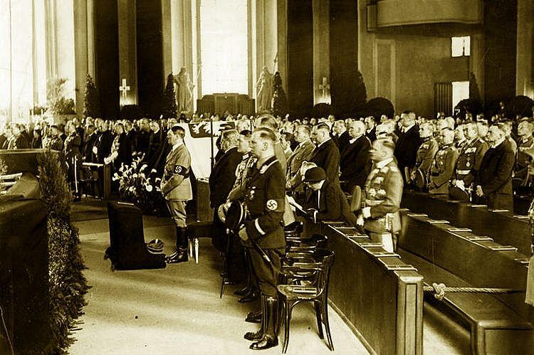 Adolf Hitler stoi obok symbolicznej trumny Józefa Piłsudskiego podczas uroczystości w katedrze św. Jadwigi (źródło: domena publiczna).