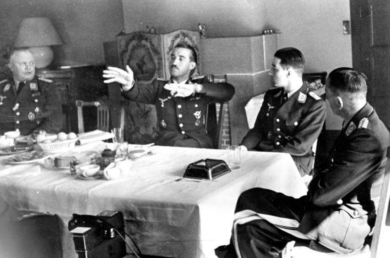 Adolf Galland gestykuluje w czasie urodzinowego przyjęcia innego asa Luftwaffe Theo Osterkampa. Kwiecień 1941 (źródło: Bundesarchiv; lic. CC ASA 3.0).