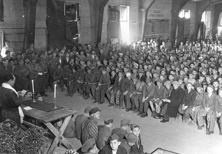Nawet wiele miesięcy po wyzwoleniu ofiary Holokaustu musiały nadal nosić obozowe pasiaki. Na zdjęciu wojskowy kapelan rabin Hershel Schaecter odprawia nabożeństwo dla były więźniów obozu w Buchenwaldzie (źródło: domena publiczna).