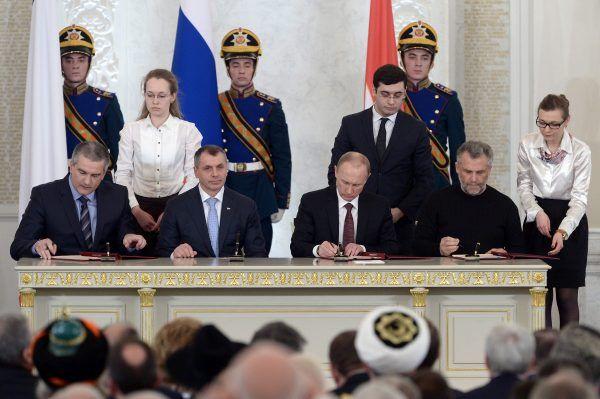 Władymir Putin i przedstawiciele Republiki Autonomicznej Krymu podpisują traktat o aneksji Krymu do Rosji (fot. Kremlin.ru, CC BY 3.0).