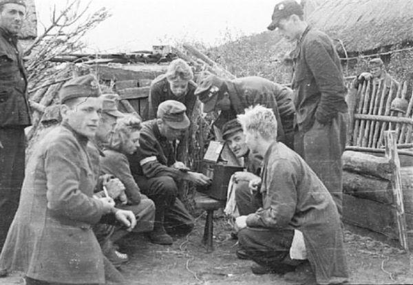 Partyzanci słuchają radia w Kampinosie (domena publiczna).