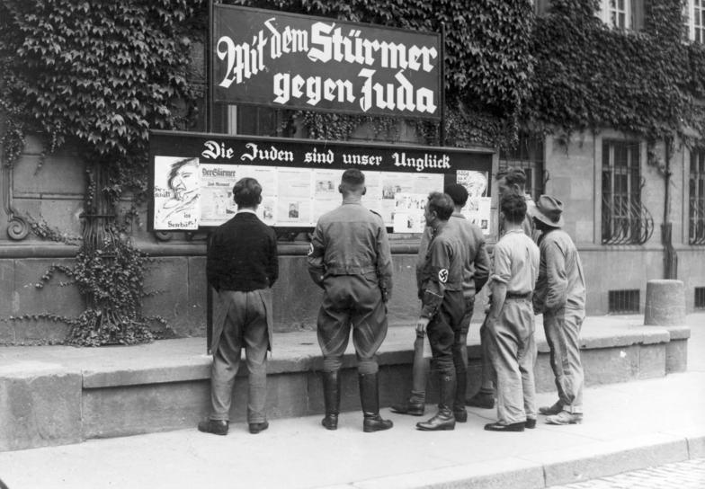 """Tygodnik """"Der Stürmer"""" był jednym z głównych narzędzi nazistów w szerzeniu antysemickich haseł. Na zdjęciu z 1933 roku mieszkańcy Wormacji czytają """"Stürmera"""" (źródło: Bundesarchiv; lic. CC ASA 3.0)."""
