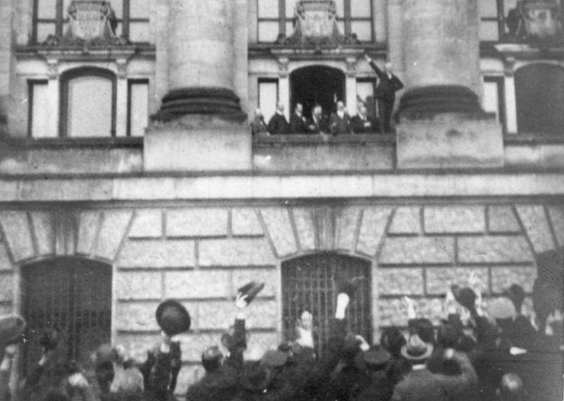 """Powołanie do życia Republiki Weimarskiej było dla wielu niemieckich nacjonalistów """"ciosem w plecy"""" zadanym przez socjaldemokratów, w szeregach których - jak podkreślano - znajdowało się wielu Żydów. Na zdjęciu Philip Scheidemann 9 listopada 1918 roku proklamuje republikę z okna gabinetu kanclerskiego (źródło: domena publiczna)."""