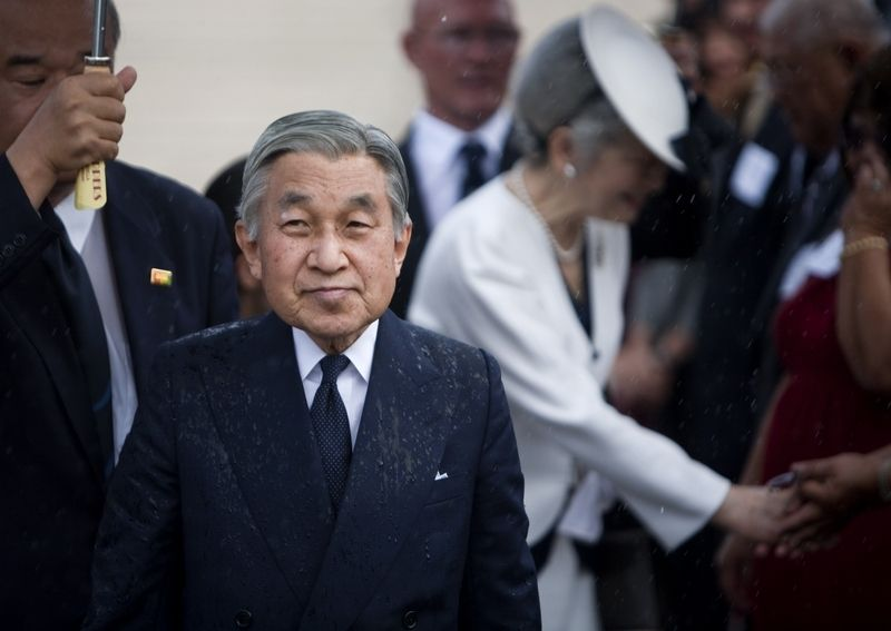 Kilka miesięcy później. Cesarz Akihito z małżonką Michiko w strugach deszczu zmierzają do Narodowego Cmentarza Pamięci w Honolulu (Oficjalne zdjęcie U.S. Marine Corps autorstwa Lance Cpl. Achilles Tsantarliotis, domena publiczna).