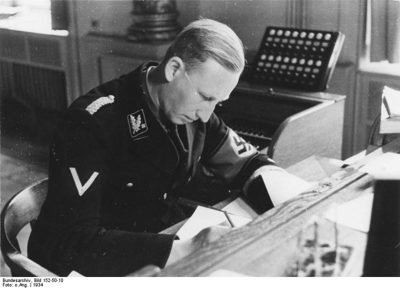 Reinhard Heydrich, jeden z architektów nocy długich noży przy biurku w Monachium w 1934 roku. A tak niewinnie wyglądał... (Bundesarchiv, Bild 152-50-10 / Friedrich Franz Bauer, lic. CC-BY-SA 3.0 de).