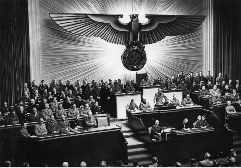"""Hitler przemawiający do Reichstagu w grudniu 1941 roku. Przywódca Niemiec wciąż udawał demokratę, choć zgromadzenie nazywano dowcipnie """"najdroższym chórem świata"""" (Bundesarchiv, Bild 183-1987-0703-507 / autor nieznany, lic. CC-BY-SA 3.0 de)."""