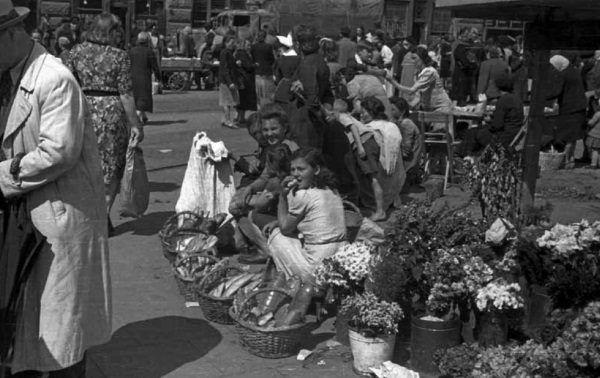 """Kobiety handlujące kwiatami i pieczywem na jednej z warszawskich ulic. Zdjęcie pochodzi z książki """"Okupacja od kuchni""""."""