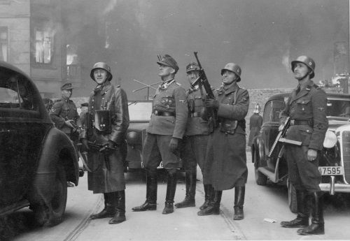"""Jürgen Stroop (pośrodku, w czapce polowej) w płonącym getcie warszawskim (1943). Swoich pomagierów z krajów bałtyckich nazywał pogardliwie """"Askarysami"""". (zdj. domena publiczna)."""