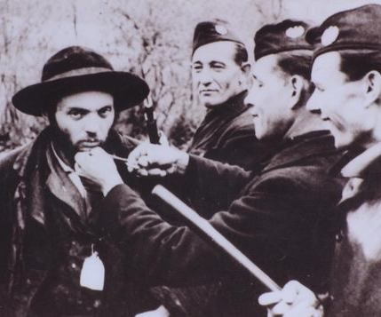 Członkowie Hlinkowej Gwardii znęcają się nad Żydem mających trafić do jednego z transportów (źródło: domena publiczna).