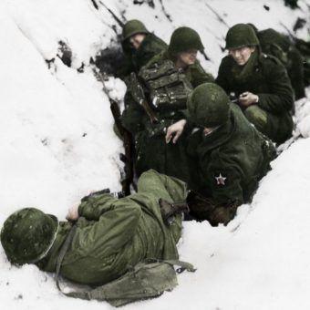 Żołnierze z amerykańskiego 9. Pułku Piechoty kryją się przed niemieckim ostrzałem artyleryjskim. Ardeny, grudzień 1944 roku (źródło: domena publiczna; koloryzacja: Rafał Kuzak).