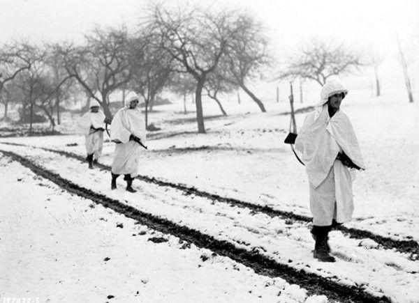 Amerykańscy żołnierze przykryci prześcieradłami na patrolu w okolicy miasteczka Lellig w Luksemburgu, 30 grudnia 1944 r. (fot. Hustead, U.S. Army Signal Corps, ze zbiorów U.S. Army Center of Military History, domena publiczna).