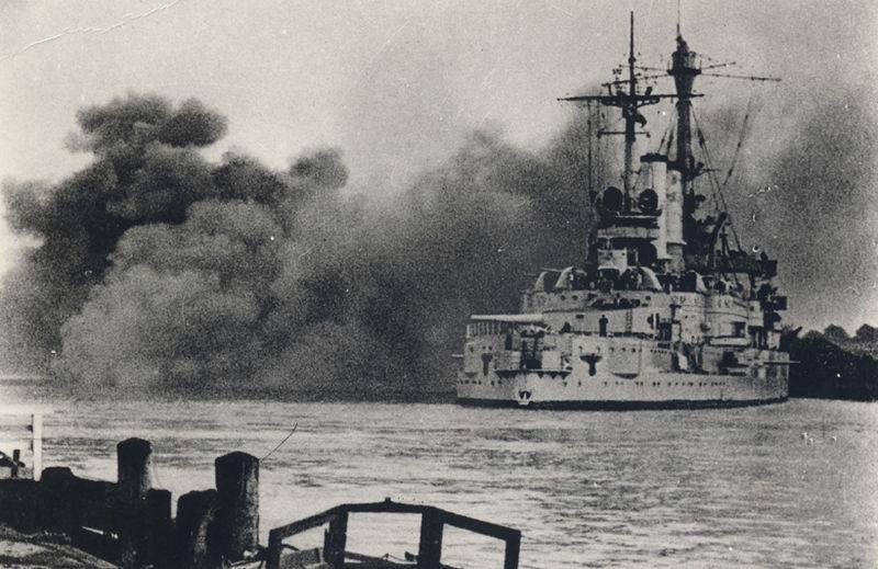 """""""Schleswig-Holstein"""" ostrzeliwuje Westerplatte. Artyleria pokładowa starego pancernika dwukrotnie (1 i 7 września) obrała sobie za cel Wojskową Składnicę Tranzytową (źródło: domena publiczna)."""