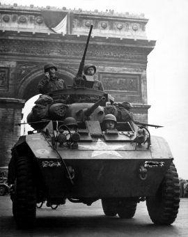 Samochód pancerny M8 Greyhound chwilę po przejechaniu pod Łukiem Tryumfalnym w Paryżu, sierpień 1944 r. (fot. ze zbiorów National Archives and Records Administration, domena publiczna).