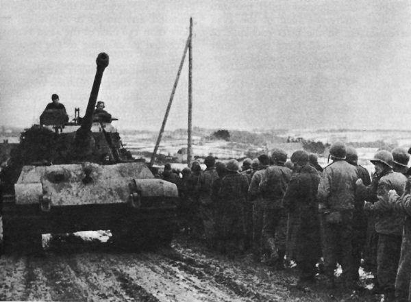 Czołg Tygrys II przejeżdża obok kolumny jeńców amerykańskich wziętych przez Niemców do niewoli w pierwszym dniu ofensywy w Ardenach (fot. ze zbiorów US Army Center for Military History, domena publiczna).