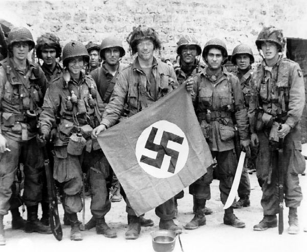 Amerykańscy spadochroniarze ze 101 Dywizji Powietrznodesantowej w pierwszych dniach inwazji w Normandii. Na pierwszym planie James Flanagan ze zdobytą nazistowską flagą w rękach (fot. U.S. Army, domena publiczna).