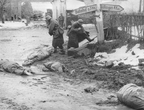 """Jeńcy amerykańscy pomordowani w Honsfeld przez Kampfgruppe Peiper. Niemiecki żołnierz przymierza """"zdobyczne"""" buty (fot. U.S. Army, ze zbiorów National Archives and Records Administration, domena publiczna)."""