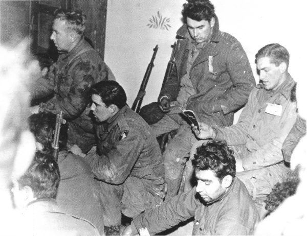 Amerykańscy spadochroniarze ze 101. Dywizji Powietrznodesantowej w Bastogne śpiewają kolędy w Wigilię Bożego Narodzenia (fot. U.S. Army, ze zbiorów National Archives and Records Administration, domena publiczna).