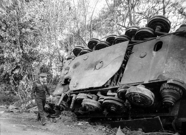 Generał Dwight D. Eisenhower, Naczelny Dowódca Alianckich Sił Ekspedycyjnych, obok przewróconego wraku Tygrysa Królewskiego (fot. Acme News Photos, domena publiczna).