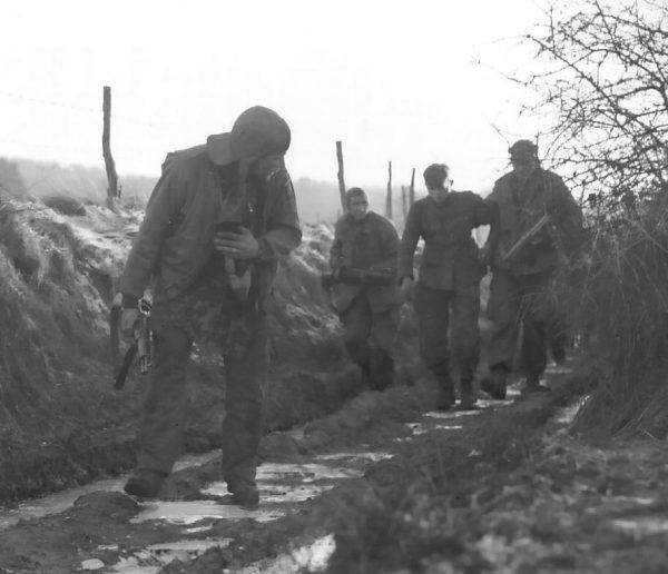 Amerykańscy żółnierze prowadzą schwytanego SS-mana. Miał szczęście, że nie został zastrzelony na miejscu (fot. domena publiczna).