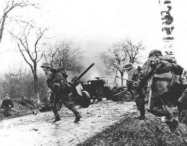Niemcy żołnierze nacierają na amerykańskie pozycje w czasie ofensywy w Ardenach, grudzień 1944 r. (fot. U.S. Army Center for Military History, domena publiczna).