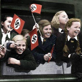 """Zdjęcie niemieckich dzieci wyjeżdżających z Berlina w ramach akcji ewakuacyjnej, mającej uratować """"przyszłość rasy panów"""" przed ewentualnym alianckim bombardowaniem (źródło: Bundesarchiv, lic.: CC-BY-SA, koloryzacja: Rafał Kuzak)."""