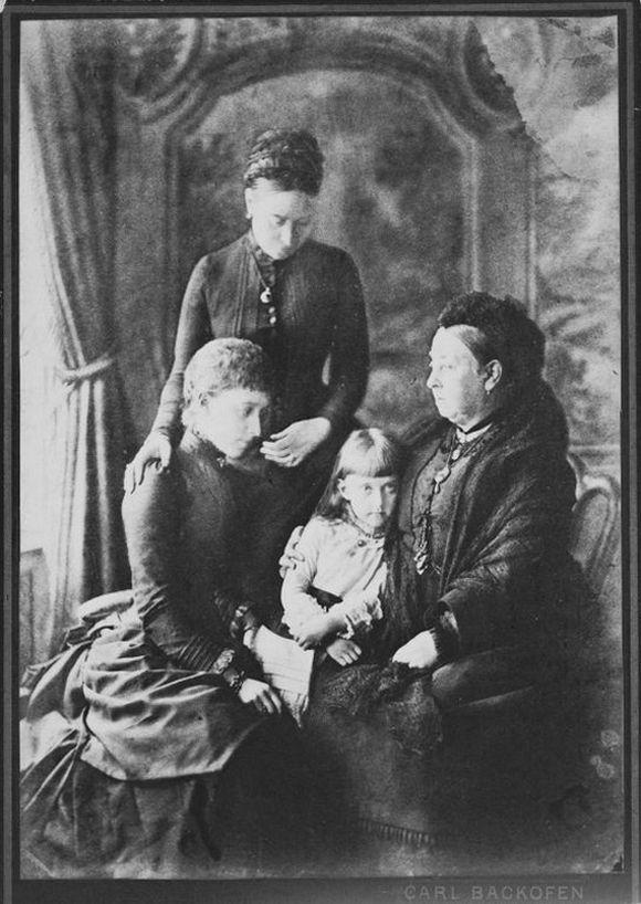 Sielankowe zdjęcie przedstawiające 4 pokolenia rodu: 65-letnią królową Wiktorię, jej 44-letnią córkę Wiktorię (stoi), 24-letnią wnuczkę Charlottę i 5-letnią prawnuczkę Feodorę. W rzeczywistości stosunki między tymi kobietami były bardzo napięte, a szczególnie relacje Charlotty i Feodory stały się wkrótce patologiczne (fot. Carl Backofen; domena publiczna).
