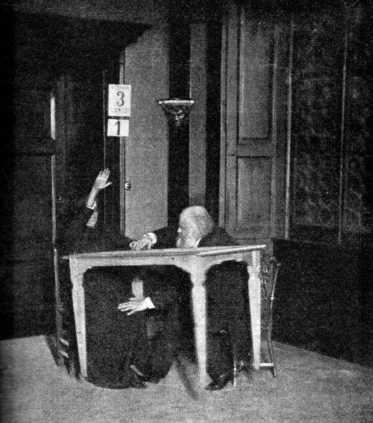 Eusapia Palladino podczas seansu spirytystycznego. Dzielnie asystuje jej Aleksandr Aksakow sprawdzając, czy nie popełnia klasycznego oszustwa z podnoszeniem stołu kolanem (źródło: domena publiczna).
