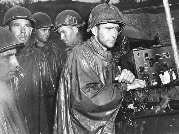 Amerykańscy żołnierze na Okinawie słuchają przez radio informacji o zakończeniu wojny w Europie, 8 maja 1945 r. (fot. U.S. military or Department of Defense, domena publiczna).