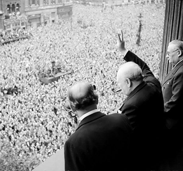 Winston Churchill pozdrawia tłumy z jednego z budynków rządowych na ulicy Whitehall (fot. domena publiczna).