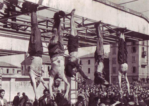 Ciała Benita Mussoliniego (drugie od lewej), Clary Petacci i trójki prominentnych faszystów powieszone na stacji benzynowej na Pizzale Loreto w Mediolanie (fot. domena publiczna)