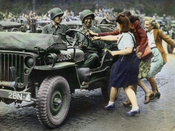 """Paryżanki biegną powitać amerykańskich żołnierzy. Prawdziwa sielanka. Często jednak rzeczywistość wyglądała zupełnie inaczej (źródło: fragment okładki książki Antony'ego Beevora """"Paryż wyzwolony"""")."""