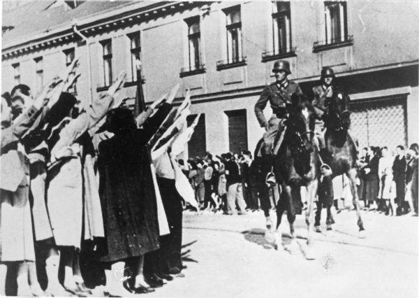 Zdjęcie propagandowe, na którym łódzcy volksdeutsche witają niemiecką kawalerię (źródło: domena publiczna).