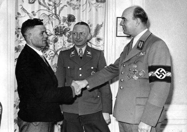 Heinz Reinefarth wykazał się w akcji Heim ins Reich. By zrobić miejsce dla Niemców ze Wschodu, trzeba było wyrzucić z domów Polaków... Na zdjęciu razem z Arthurem Greiserem (po prawej) wita milionowego Niemca przesiedlonego do Kraju Warty (źródło: Bundesarchiv, lic.: CC BY-SA 3.0 de).