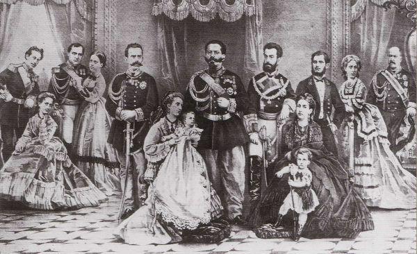 Wielka szczęśliwa rodzina króla Włoch... która udaje, że pod koniec maja 1867 roku nic takiego się nie wydarzyło. Na tym rysunku z 1870 roku Amadeusz (z brodą) stoi po lewicy ojca, obok niego na krześle siedzi Maria Wiktoria z ich pierworodnym synkiem przy sukni (źródło: domena publiczna).