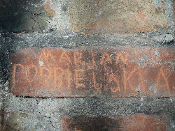 Napis wyryty przez jednego z więźniów w jednej z cel dawnej siedziby Wojewódzkiego Urzędu Bezpieczeństwa Publicznego w Warszawie, w kamienicy na ulicy Strzeleckiej 8 (fot. Kacper.jackiewicz.1998, CC BY-SA 3.0 PL).