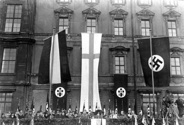 """Wielu duchownych, zarówno luterańskich jak i katolickich popierało nazistów, ale jeszcze więcej było biernych kapłanów, którzy nie odważyli się skrytykować nazistowskich zbrodni. Na zdjęciu obchody Dnia Lutra w Berlinie zorganizowane popierającą nazistów protestancką organizację """"Deutsche Christen"""" (źródło: Bundesarchiv, Bild 102-15234, licencja: CC-BY-SA 3.0)."""