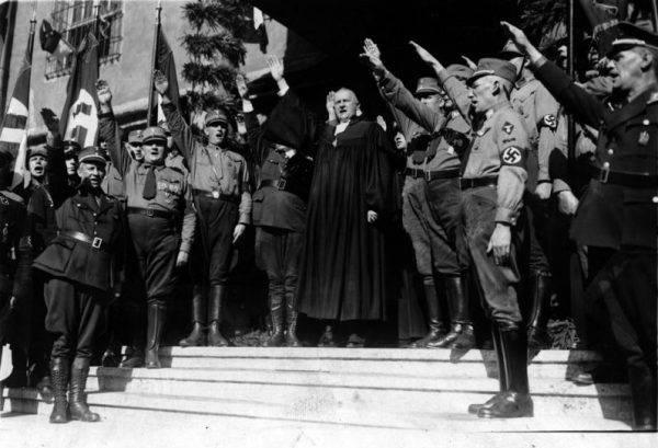 Otwarcie Narodowego Synodu w Wittenberdze. W środku Ludwig Müller, Reichsbischof Ewangelickiego Kościoła Niemieckiego i członek organizacji Deutsche Christen (źródło: Bundesarchiv, Bild 183-H25547, licencja: CC-BY-SA 3.0).