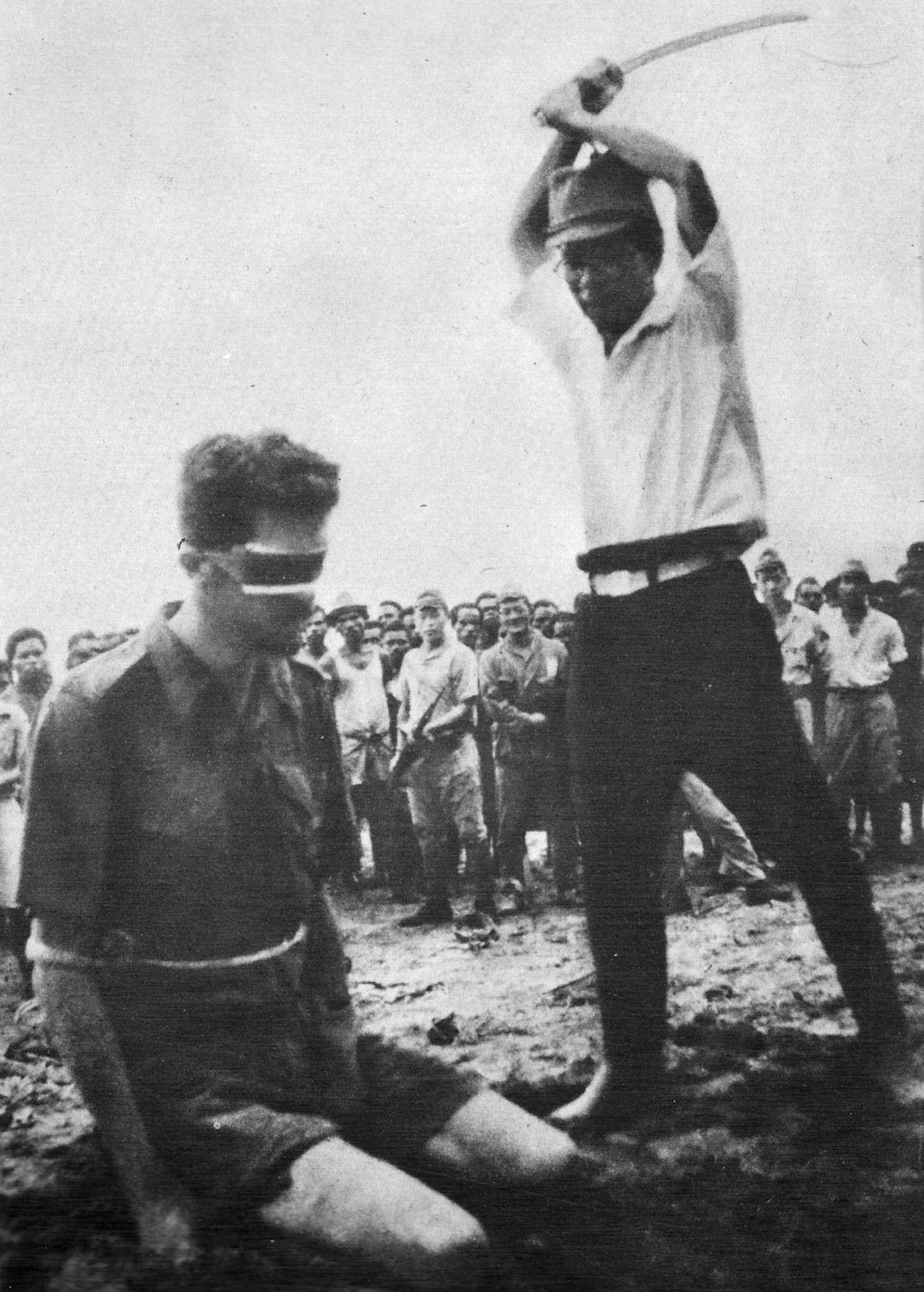 """Zmaltretowane ludzkie """"kłody"""" pozbawiano życia między innymi poprzez ścięcie. Na zdjęciu australijski komandos, sierżant Leonard G. Siffleet, tuż przed śmiertelnym ciosem zadanym przez Japończyka Yasuno Chikao w październiku 1943 roku (źródło: Collection Database of the Australian War Memorial, domena publiczna)."""