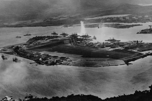 """Fotografia z japońskiego samolotu na początku ataku na Pearl Harbor. Eksplozja w środku zdjęcia to trafienie torpedy w USS """"West Virginia"""" (źródło: Official U.S. Navy photograph NH 50930., domena publiczna)."""