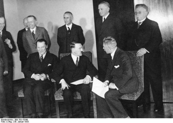 W 1933 roku Hitler z polityka wiecowego musiał przedzierzgnąć się w gabinetowego. Jednak wcale nie chciał zrezygnować dla władzy ze swobody robienia, czego chce. Nawet podczas pozowania do zdjęcia ze swym świeżo sformowanym gabinetem nie mógł się powstrzymać od gardłowania z wicekanclerzem von Papenem (Bundesarchiv, Bild 102-15348 / CC-BY-SA 3.0).