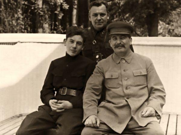 """Wasilij Stalin z """"oboma"""" ojcami - Józefem Stalinem i Nikołajem Własikiem - w 1935 roku (domena publiczna)."""
