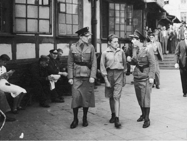 Policjantki prowadzą młodego kieszonkowca do izby zatrzymań ulicami Warszawy roku 1939 (źródło: domena publiczna).