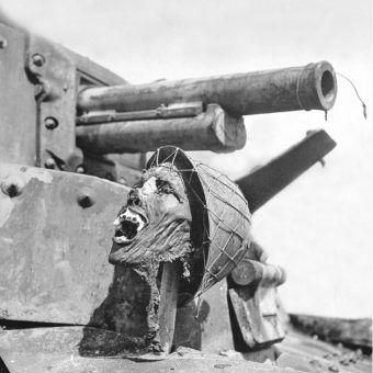 """Odcięta głowa spalonego napalmem żołnierza japońskiego zatknięta poniżej działa dobytego japońskiego czołgu. Zdjęcie i podpis z książki """"Historia świata przez ścięte głowy opisana"""" (Bellona 2017)."""