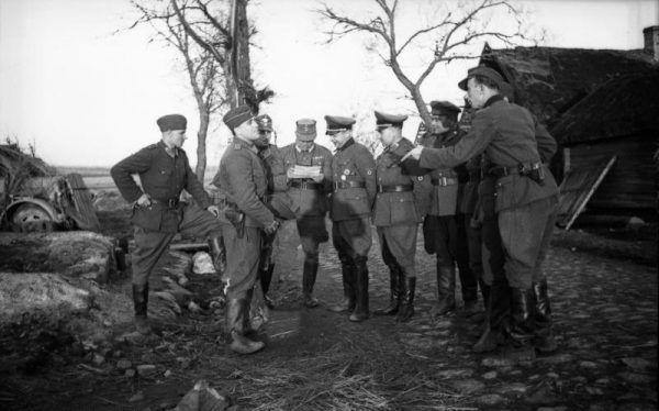 Na fotografii Bronisław Kamiński rozmawia z niemieckimi policjantami i członkami RONA podczas antypartyzanckiej akcji na Białorusi w 1944 roku.