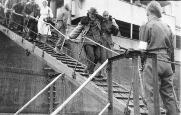 Niemieccy uchodźcy schodzą ze statku w porcie zajętym przez wojska brytyjskie.