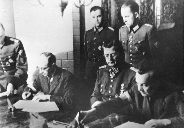 """Podpisanie """"Układu o zaprzestaniu działań wojennych w Warszawie"""", 3 października 1944 roku. W środku siedzi generał von dem Bach, a obok niego dwóch powstańców: po lewej pułkownik Kazimierz Iranek-Osmecki """"Heller"""", po prawej podpułkownik Zygmunt Dobrowolski """"Zyndram""""."""