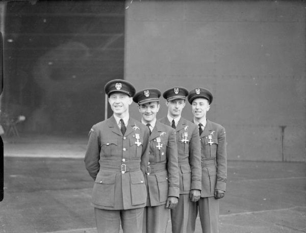 Na zdjęciu Witold Urbanowicz, Jan Zumbach, Mirosław Ferić, Zdzisław Henneberg z przypiętymi brytyjskimi odznaczeniami po ceremonii ich wręczenia. (domena publiczna)