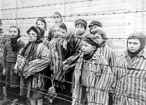 Wystarczyło zniszczyć wszelkie materialne ślady po człowieku, by w przenośni i dosłownie zniknął on z powierzchni ziemi... Na zdjęciu dzieci za drutami obozu. Kadr z filmu sowieckiego dokumentującego wyzwolenie Auschwitz.