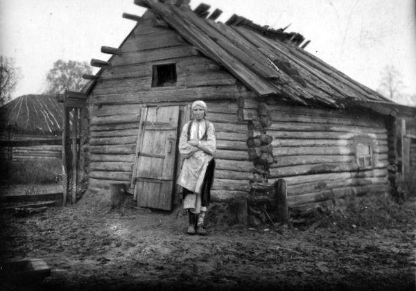 Kobieta z powiatu sarneńskiego obok swojego walącego się domu. Choć dziś nie chcemy o tym pamiętać, ogromne rzesze ludności żyły w skrajnej biedzie.